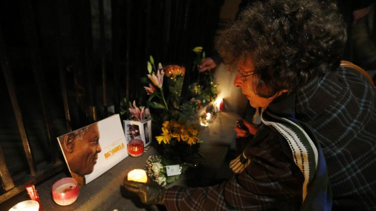 Woman lights a candle at a gathering in memory of Nelson Mandela outside the South African High Commission across from Trafalgar Square in London