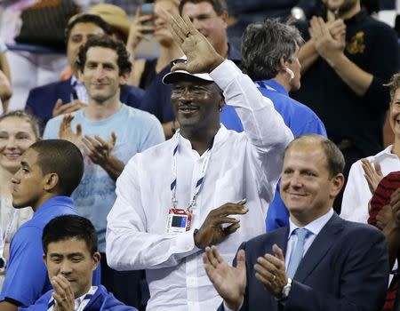 Former basketball great Jordan waves to Federer of Switzerland during the men's singles match at the U.S. Open tennis tournament in New York
