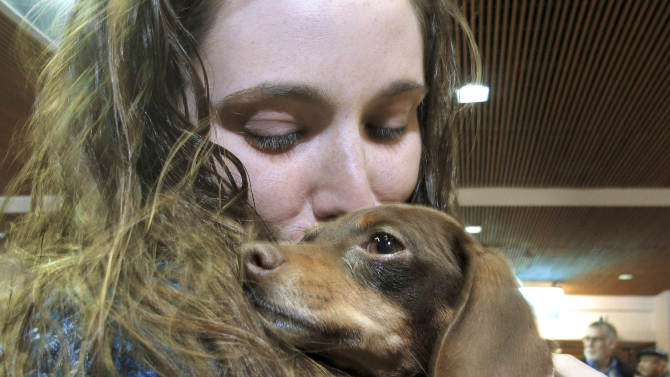 Mandi Smith, of Fort Campbell, Ky.,is reunited with her dog, Pooka, Wednesday, Jan. 30, 2013 at the Albuquerque International Sunport Airport in Albuquerque, N.M.  The Chihuahua-dachshund mix, also known as a chiweenie, disappeared from her yard 18 months ago and was found wandering the streets 1,200 miles away inEspanola, N.M.,in January. The dog was traced to Smith by her microchip, but how she got to New Mexico is a mystery. (AP Photo/Jeri Clausing)
