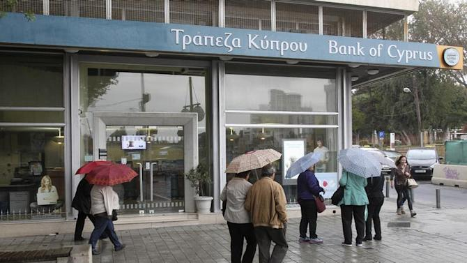 Cypriots walk outside Bank of Cyprus branch on the island's capital Nicosia