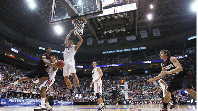 Harvard's Siyani Chambers, left, passes to his teammate Jonah Travis, right, as Arizona's Jordin Mayes, second from left, Brandon Ashley (21) and Kaleb Tarczewski (35) defend during the first half in a third-round game in the NCAA men's college basketball tournament in Salt Lake City on Saturday, March 23, 2013. (AP Photo/George Frey)