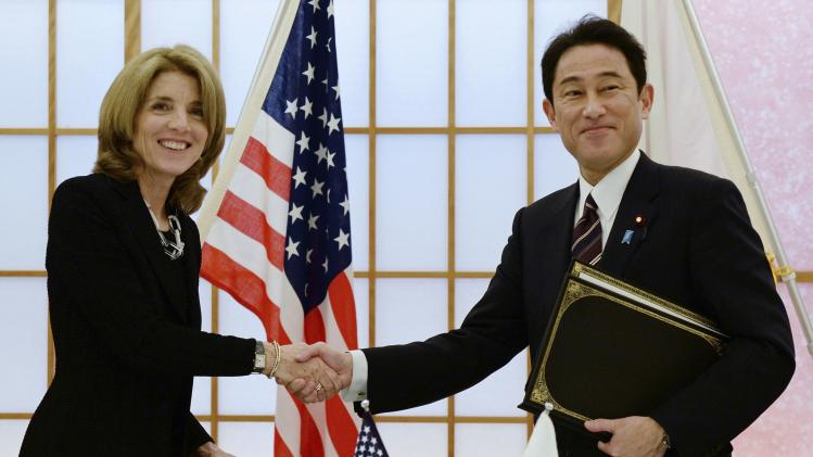 U.S. Ambassador to Japan Kennedy shakes hands with Japan's Foreign Minister Kishida after exchanging documents in Tokyo