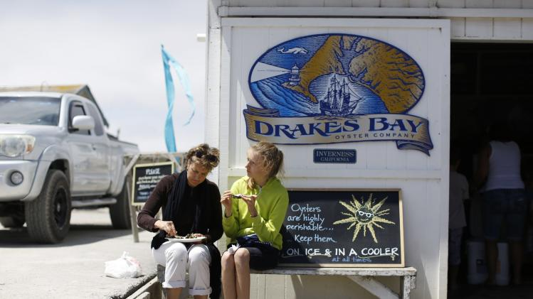 Two customers enjoy oysters outside the oyster shack at Drakes Bay Oyster Company in Inverness, California