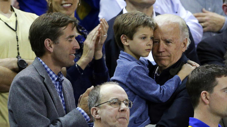 Vice President Joe Biden, right, holds his grandson Hunter next to his son, Beau, while watching a second-round game between Delaware and North Carolina in the women's NCAA college basketball tournament in Newark, Del., Tuesday, March 26, 2013. (AP Photo/Patrick Semansky)