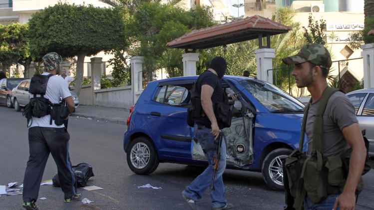 Gunmen and followers of a radical Sunni cleric Sheik Ahmad al-Assir, inspect a damaged car after clashes erupted, in the southern port city of Sidon, Lebanon, Tuesday, June 18, 2013. Heavy clashes erupted Tuesday between unknown gunmen and followers of a radical Sunni cleric in south Lebanon, security officials said, killing several people in the latest apparent outbreak of violence between Lebanese factions supporting opposing sides in the civil war in neighboring Syria. (AP Photo/Mohammed Zaatari)