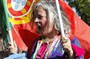 A woman with a Portuguese flag shouts slogans during a protest against austerity in front of the presidential palace in Lisbon