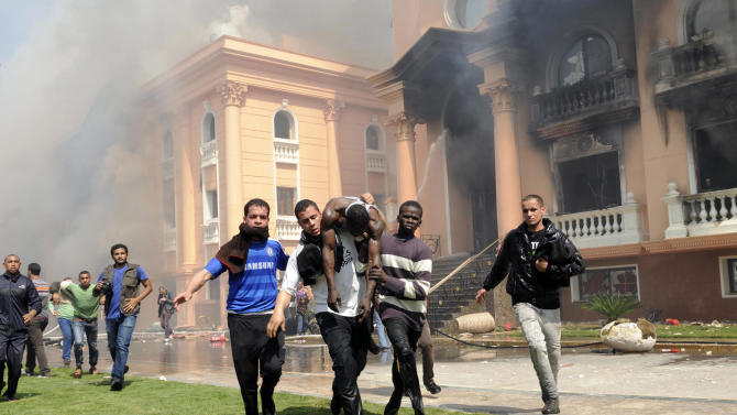 An injured security official is carried from a police officers club in the upscale neighborhood of Zamalek, after protesters set fires following a court verdict in Cairo, Saturday, March 9, 2013. Fans of Cairo's Al-Ahly club have stormed Egypt's soccer federation headquarters and the nearby police club, and set them ablaze after a court acquitted seven of nine police official on trial for their alleged part in deadly stadium melee. (AP Photo/Mohammed Asad)