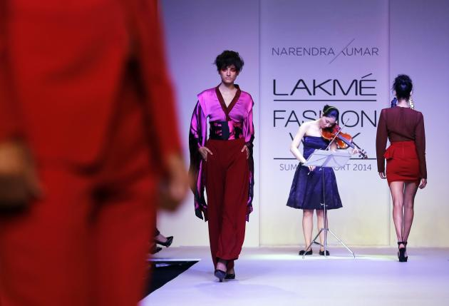 A musician plays the violin as models display creations by Narendra Kumar during the Lakme Fashion Week in Mumbai, India, Wednesday, March 12, 2013. (AP Photo/Rajanish Kakade)