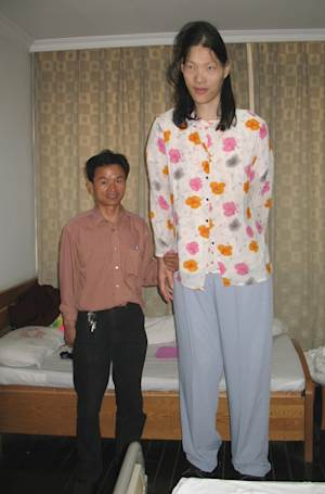 FILE - In this May 12, 2006 file photo released by China's Xinhua News Agency, Yao Defen, right, who is 7 feet and 7 inches (233.3 centimeters) tall poses for a photo with her elder brother in a hospital affiliated to Anhui Medical University where she is having a physical examination, in Hefei, the capital of east China's Anhui Province. The world's tallest woman has died in eastern China. She was 39. Chinese state media say Yao died on Nov. 11, 2012, at her home in China's eastern province of Anhui.  (AP Photo / Xinhua, Wang Shilong, File) NO SALES