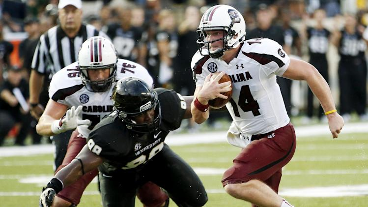 South Carolina quarterback Connor Shaw (14) gets away from Vanderbilt's Johnell Thomas (98) in the first half of an NCAA college football game, Thursday, Aug. 30, 2012, in Nashville, Tenn. (AP Photo/John Russell)