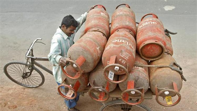 A worker loads Liquefied Petroleum Gas (LPG) cylinders onto his cycle-rickshaw in Kolkata January 17, 2013. REUTERS/Rupak De Chowdhuri/Files