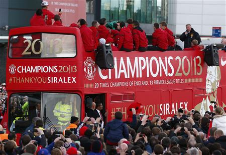 Retiring Manchester United manager Alex Ferguson speaks to the crowd from the rear of a double decker bus during the team's English Premier League victory parade outside Old Trafford stadium in Manche