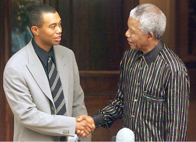 Then South African President Nelson Mandela (R) shakes hands with US golfer Tiger Woods, on November 30, 1998 after receiving him at his Johannesburg residence