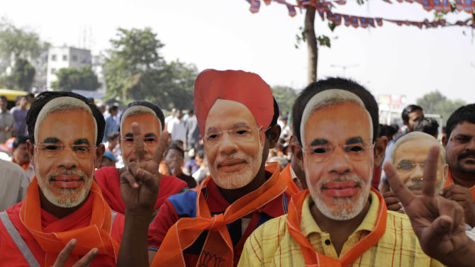 In this Nov. 30, 2012 photo, Indian supporters of Gujarat Chief Minister Narendra Modi wearing his masks gesture during a public meeting Modi addressed before filing his nomination for state assembly elections in Ahmadabad, India. Eleven years after Modi became the chief minister of the western state of Gujarat - and 10 years after brutal anti-Muslim rioting left over a 1,100 people there dead - Modi is campaigning for his third term. Nearly everyone expects him to be swept into office, and the top leadership of his rightwing Bharatiya Janata Party is already hailing him as a future prime minister. But few politicians in India are as polarizing as Modi. (AP Photo/Ajit Solanki)