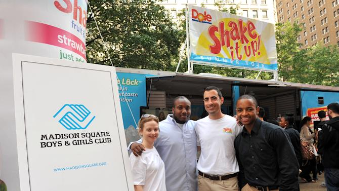 Vanessa Beltran, left, and Paul Panza, second right, of Dole Foods, celebrate the donation of healthy snacks with Madison Square Boys & Girls Club representatives Jarrell Hughes, second left, and Tru Garland, right, winner of the Joel E. Smilow Clubhouse Youth of the Year award, at the DOLE Shake It Up!  Summer Tour in New York's Herald Square, Wednesday, May 16, 2012.   (Diane Bondareff/AP Images for DOLE)