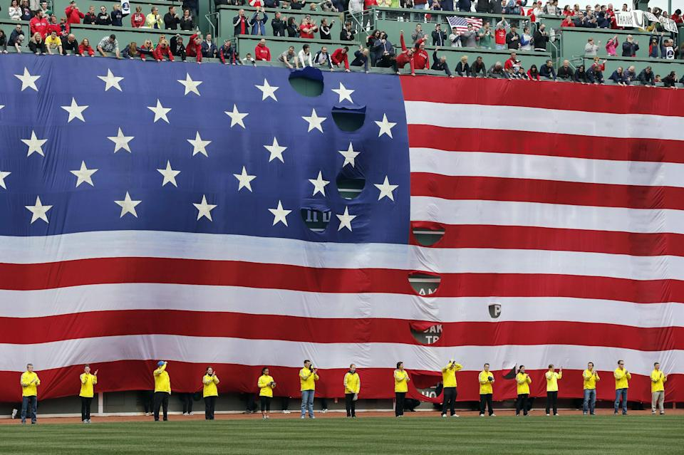 Boston Marathon volunteers stand beneath a giant flag on the outfield wall during a tribute to victims of the Boston Marathon bombings, before a baseball game between the Boston Red Sox and the Kansas City Royals in Boston, Saturday, April 20, 2013. (AP Photo/Michael Dwyer)