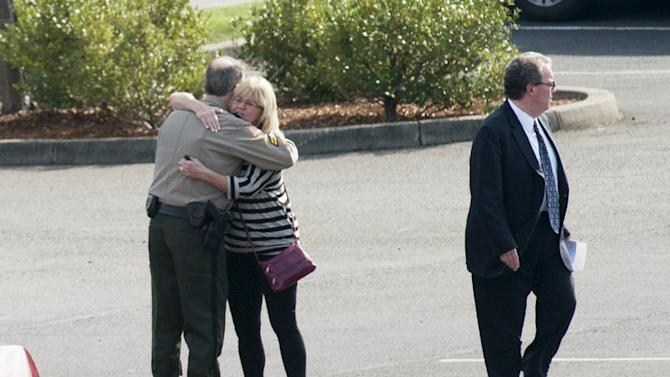 People hug as they leave the funeral service of Umpqua Community College student Jason Johnson in Roseburg