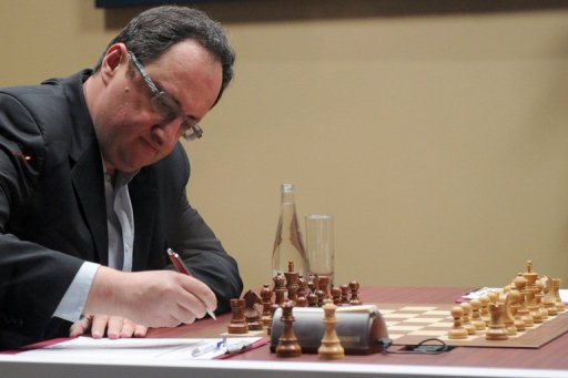 At the board, Boris Gelfand puts his head in his hands, runs fingers through his hair or puts his forehead on the table