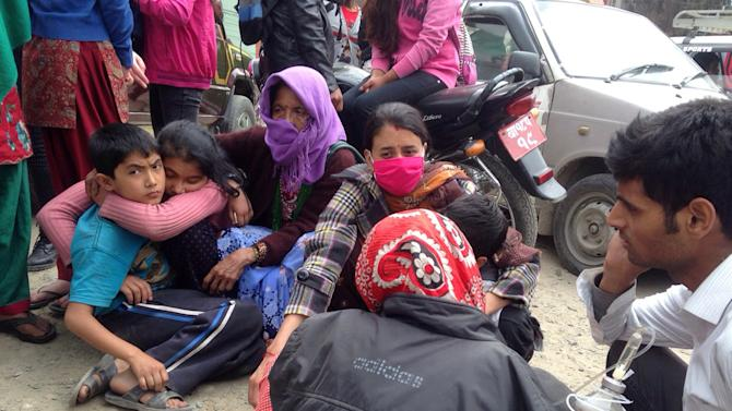 Nepalese people huddle together outside the Medicare Hospital in Kathmandu, Nepal, Saturday, April 25, 2015. A strong magnitude-7.9 earthquake shook Nepal's capital and the densely populated Kathmandu Valley before noon Saturday, causing extensive damage with toppled walls and collapsed buildings, officials said. (AP Photo/ Niranjan Shrestha)