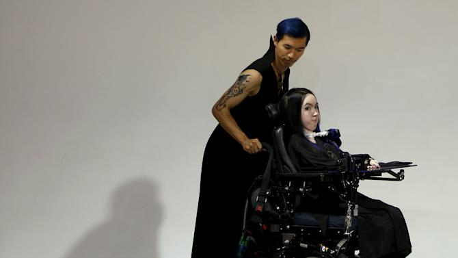 French model, who is a spinal muscular atrophy patient, is pushed in a wheelchair as she presents a creation by designer Tsuruta from his Spring/Summer 2016 collection for his brand tenbo during Tokyo Fashion Week in Tokyo, Japan