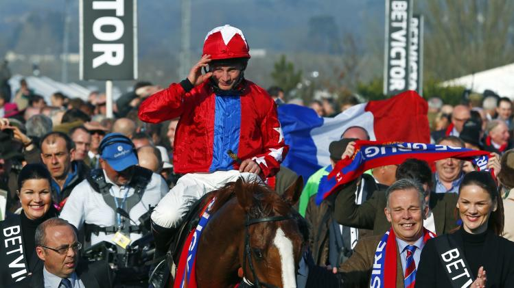 Jamie Moore on Sire De Grugy celebrates winning the Queen Mother Champion Steeple Chase at the Cheltenham Festival horse racing meet in Gloucestershire