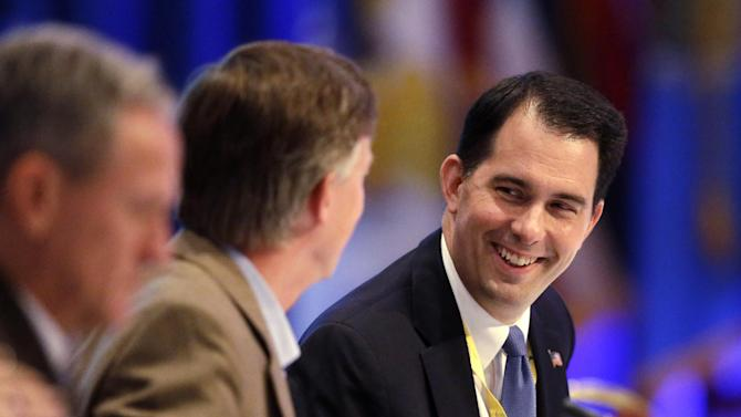 Wisconsin Gov. Scott Walker, right, talks to Colorado Gov. John Hickenlooper during a session of the National Governors Association meeting Sunday, August, 4, 2013 in Milwaukee. Republicans have stated openly they plan to use the slow economic recovery and the health care law to attack Democrats in the 2014 congressional elections. (AP Photo/Morry Gash)
