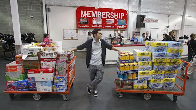 FILE-In this Wednesday, May 9, 2012, file photo, David Lee holds on to his carts while shopping at a Costco Wholesale in Portland, Ore. A steep drop in gasoline costs drove down a measure of U.S. wholesale prices in May by the most since July 2009. But outside the food and energy categories, prices increased moderately. (AP Photo/Rick Bowmer, File)