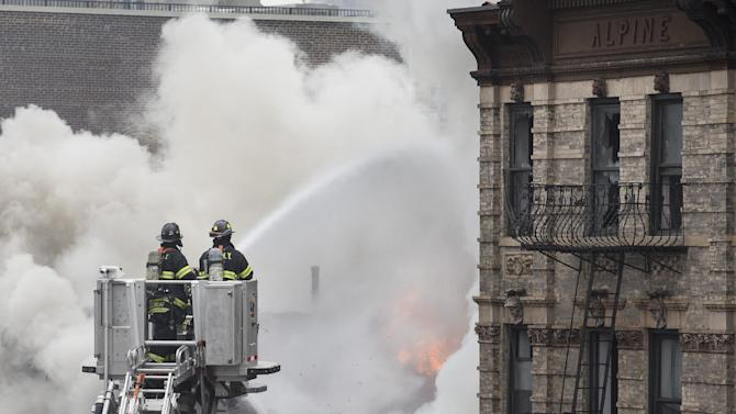 Firefighters spray water on a collapsed building in New York's East Village, Thursday, March 26, 2015, in New York. An apparent gas explosion leveled an apartment building, partially destroyed another and launched rubble and shards of glass across streets in the heart of Manhattan on Thursday, injuring at least a dozen people. (AP Photo/John Minchillo)