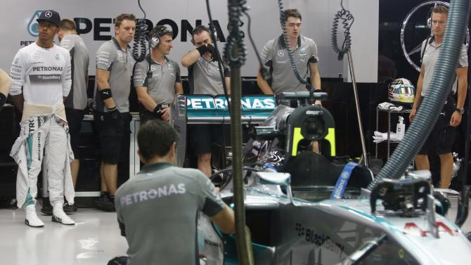 Mercedes Formula One driver Lewis Hamilton of Britain watches as team members work on his car before the second practice session of the Singapore F1 Grand Prix at the Marina Bay street circuit in Singapore