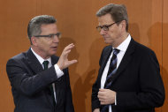 German Defence Minister Thomas de Maiziere, left, and German Foreign Minister Guido Westerwelle , right, talk as they arrive for the weekly cabinet meeting at the chancellery in Berlin, Germany, Thursday, Dec. 6, 2012. Germany's Cabinet on Thursday approved sending German Patriot air defense missiles to Turkey to protect the NATO member against possible attacks from Syria, in a major step toward possible Western military role in the Syrian conflict. Defense Minister Thomas de Maiziere told reporters that two batteries with a total of 400 soldiers would be sent to the border area under NATO command for one year, although the deployment could be shortened. The decision must be endorsed by the German Parliament, but approval is all but assured. (AP Photo/Michael Sohn)