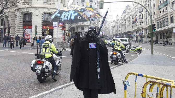 A person dressed in a Darth Vader costume watches as a demonstration of health workers passes by in Madrid, Monday Jan. 7, 2013. (AP Photo/Paul White)