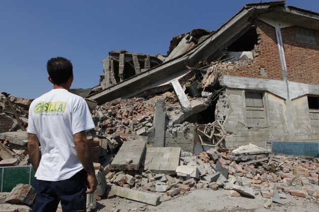 A man looks at a collapsed farm in Camposanto, northern Italy, Tuesday, May 29, 2012. A magnitude 5.8 earthquake struck the same area of northern Italy stricken by another fatal tremor on May 20.  (AP