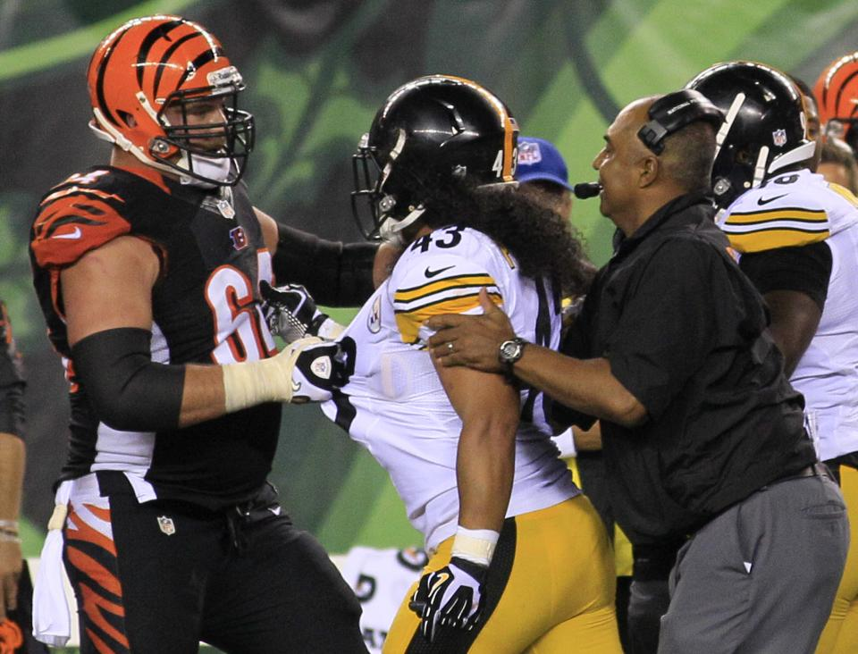 Cincinnati Bengals head coach Marvin Lewis separates center Kyle Cook (64) and Pittsburgh Steelers strong safety Troy Polamalu in the second half of an NFL football game, Monday, Sept. 16, 2013, in Cincinnati. Cincinnati won 20-10. (AP Photo/Tom Uhlman)