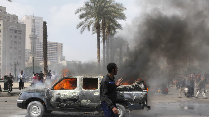 An Egyptian walks by a burning police vehicle, which has been set afire by angry protesters in Tahrir Square, once the epicenter of protests against former President Mubarak, in Cairo, Egypt, Monday, March 18, 2013. Egypt is currently mired in another wave of protests, clashes and unrest that have plagued the country since the ouster of authoritarian leader Hosni Mubarak in the pro-democracy uprising two years ago. (AP Photo/Amr Nabil)