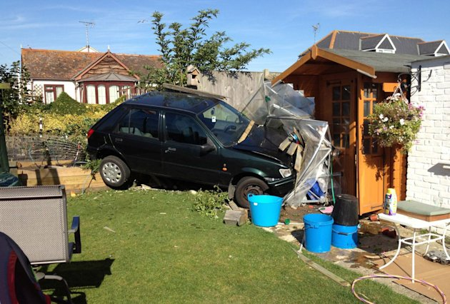 The woman driver ploughed through a wall before landing the Ford Fiesta in this garden in Herne Bay, Kent.  Picture: SWNS