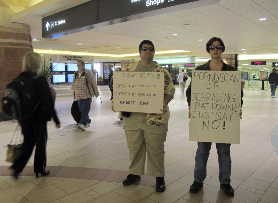 Patricia Stone and her husband John Richards of Chandler hold signs Wednesday, Nov. 24, 2010 at Phoenix Sky Harbor International Airport to protest body scanners and thorough pat-downs. (AP Photo/Amanda Lee Myers)
