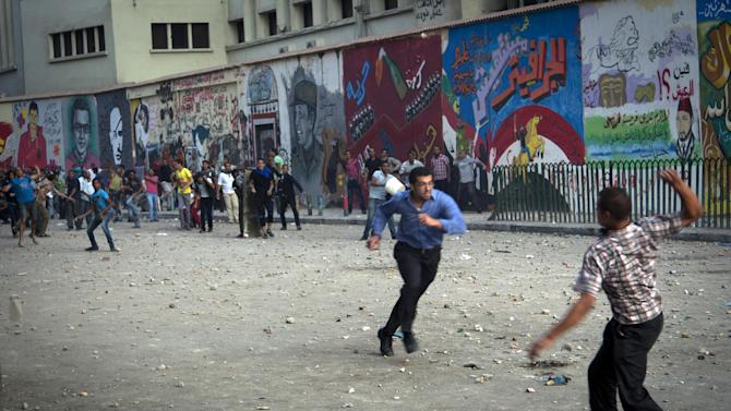 Protesters throw stones after scuffles broke out between groups of protesters in Tahrir square when chants against the new Islamist president angered some in the crowd in Cairo, Egypt, Friday, Oct. 12, 2012. Thousands of supporters and opponents of Egypt's new Islamist president clashed in Cairo's Tahrir Square on Friday, hurling stones and concrete and swinging sticks at each other in the first such violence since Mohammed Morsi took office more than three months ago.(AP Photo/Khalil Hamra)