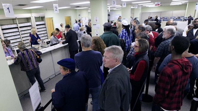 FILE - This Oct. 2,2012 file photo shows voters wait in line to pick up their ballots inside the Hamilton County Board of Elections after it opened for early voting, Tuesday, in Cincinnati. Stock up on munchies and make sure the batteries in your TV remote are fresh. With this year's presidential election razor-close to the finish, Tuesday could be a long night. Even if the presidency isn't decided until after midnight EST, there will be plenty of clues early in the evening on how things are going for President Barack Obama and Republican Mitt Romney. Obama has more options for piecing the 270 electoral votes needed for victory, so any early setbacks for Romney could be important portents of how the night will end.   (AP Photo/Al Behrman, File)