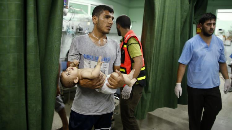 A Palestinian boy is carried at a hospital in the northern Gaza Strip