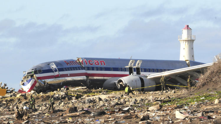 FILE - In this Dec. 23, 2009, file photo, workers sift through debris surrounding the fuselage of American Airlines flight AA331 which crash landed overnight on a flight from Miami to Jamaica, just beyond the runway of Norman Manley International Airport, in Kingston Jamaica. An investigation into a plane accident almost five years ago at a Jamaican airport has concluded that an American Airlines jet flying in from Miami botched the landing and the flight crew may have been fatigued. (AP Photo/Lloyd Robinson, File) JAMAICA OUT
