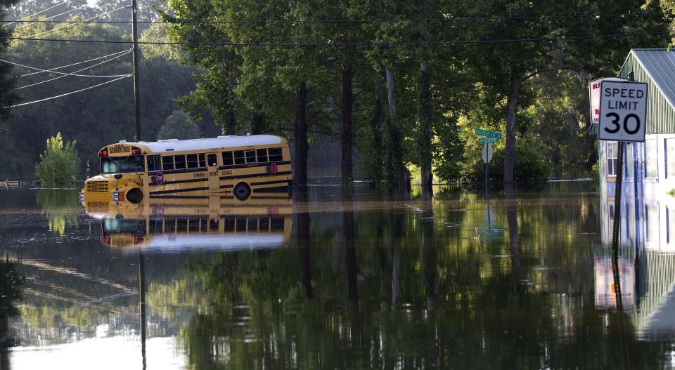 A school bus sits in flood waters near downtown Live Oak Fla., Wednesday, June 27, 2012. Dozens of homes and much of the downtown area was flooded by torrential rains from Tropical Storm Debby.  (AP Photo/Dave Martin)