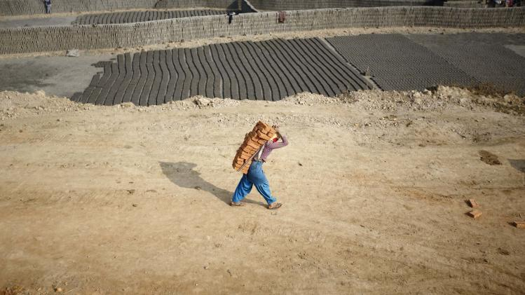 A girl carries bricks to load in a truck for delivery to a brick factory in Lalitpur
