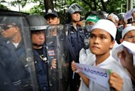 Muslim protesters confront Thai police officers during a protest against the incendiary anti-Islam film &quot;Innocence of Muslims&quot; outside the US embassy in Bangkok. Several hundred Muslims rallied outside the embassy and Google offices in the Thai capital to denounce the film