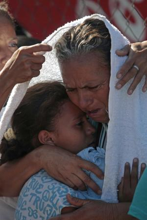 Elsa Ucles and her daughter Rosario Serrano embrace after attending the burial service for her husband Jose Serrano as they wait in line to visit surviving relatives at the prison in Comayagua, Honduras, Saturday Feb. 18, 2012.  Jose Serrano died in the fire that swept through the Comayagua prison north of Tegucigalpa late Tuesday, killing over 300 people. (AP Photo/Esteban Felix)