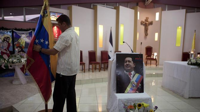 "A man prepares a Venezuelan flag next to an image of Venezuela's President Hugo Chavez before a mass in support of him in Managua, Nicaragua, Wednesday Dec. 12, 2012. Venezuela's Information Minister Ernesto Villegas expressed hope about Chavez returning home for his Jan. 10 swearing-in for a new six-year term after his cancer surgery in Cuba, but said in a written message on a government website that if Chavez doesn't make it, ""our people should be prepared to understand it."" (AP Photo/Esteban Felix)"