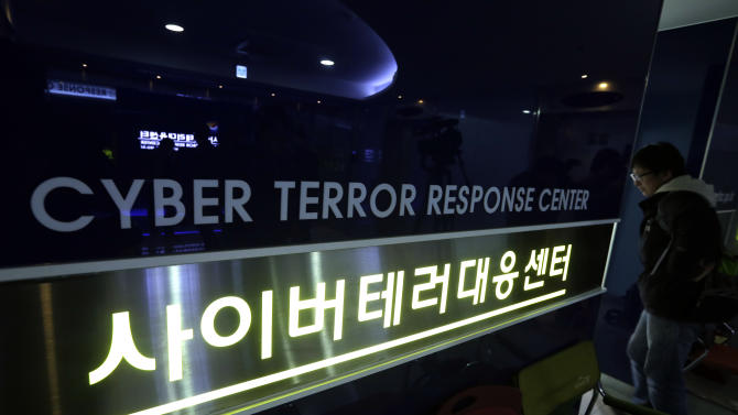A man walks past next to a sign of Cyber Terror Response Center at National Police Agency in Seoul, South Korea, Thursday, March 21, 2013. A Chinese Internet address was the source of a cyberattack on one company hit in a massive network shutdown that affected 32,000 computers at six banks and media companies in South Korea, initial findings indicated Thursday. (AP Photo/Lee Jin-man)