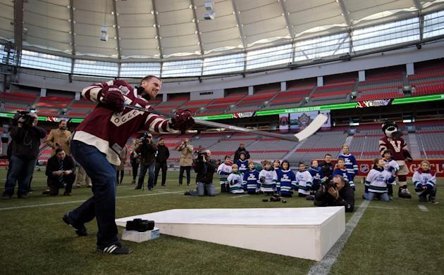 Vancouver Canucks' Daniel Sedin, of Sweden, attempts to shoot a puck through the football uprights during a media availability during a media availability to promote the 2014 NHL Heritage Classic