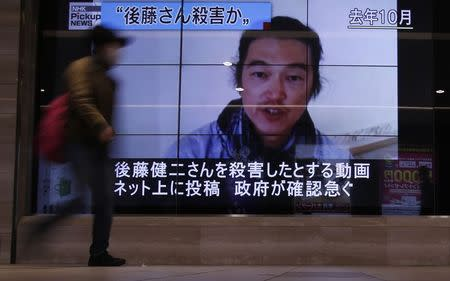 File photo of a pedestrian walking past television screens displaying a news programme about Japanese journalist Kenji Goto on a street in Tokyo