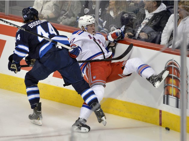 New York Rangers' Miller is checked into boards by Winnipeg Jets' Bogosian during NHL hockey game in Winnipeg