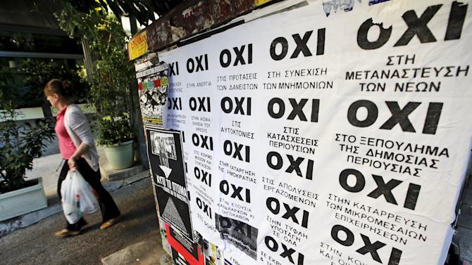 "A woman walks past referendum campaign posters reading ""No"" in Greek in Athens"